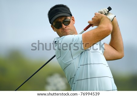 Male golfer tees off during his round - stock photo