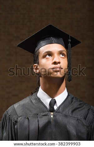 Male graduate looking up - stock photo