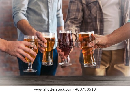 Male group clinking glasses of dark and light beer at the table - stock photo
