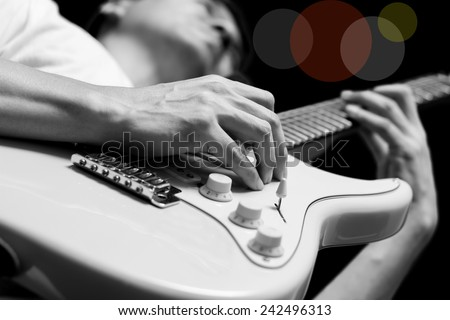 male guitarist / musician plays electric guitar, isolated on black / black and white film processed & colorful bokeh - stock photo