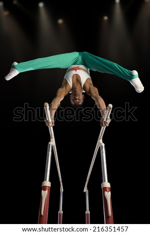 Male gymnast performing on parallel bars, low angle view - stock photo