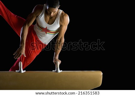 Male gymnast performing on pommel horse - stock photo