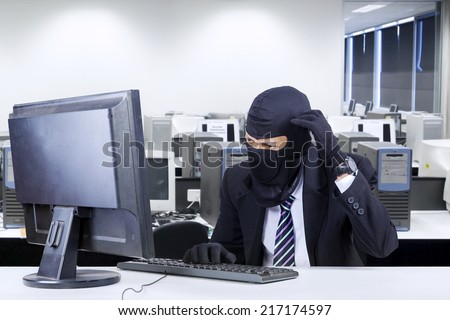 Male hacker wearing business suit getting confused to break the computer security - stock photo