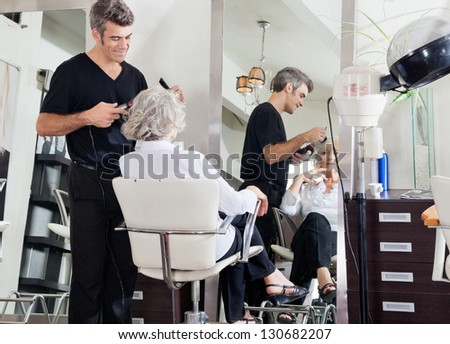 Male hairdresser styling senior woman's hair at beauty salon - stock photo