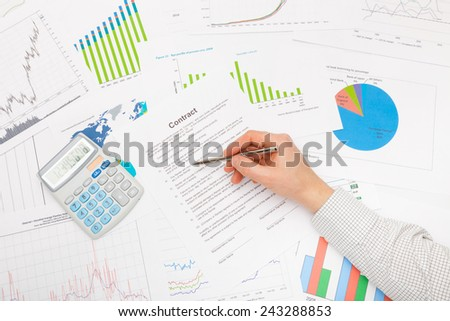 Male hand and financial charts and graphs - stock photo