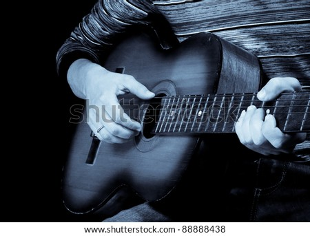 male hand and guitar isolated on black background - stock photo