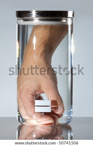 Male hand and in medical or lab container; represents medical industry technology of the ''21st century''; i.e. limb regeneration, limb reattachment possibilities - stock photo
