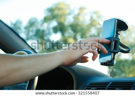 Male hand and smartphone in a car - stock photo