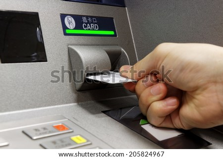 male hand businessman inserts credit card into the ATM and withdraws money  - stock photo
