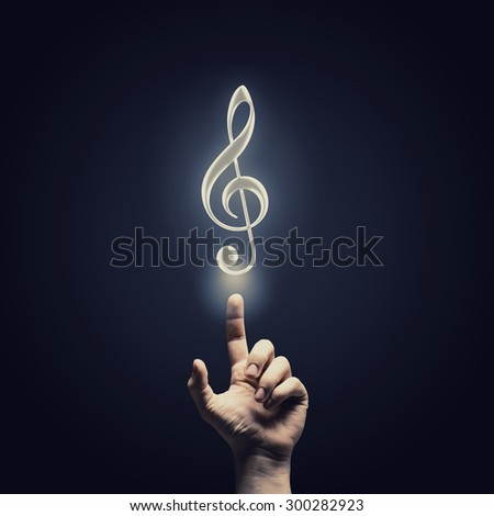 Male hand choosing music note symbol from media icons - stock photo