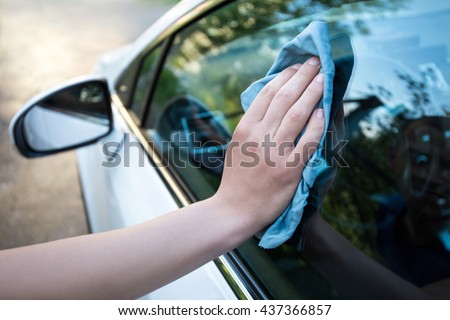 male hand cleaning car window with blue microfiber cloth - stock photo