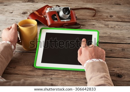 Male hand clicks then blank screen tablet computer on the wooden table and holding a cup of coffee closeup. Next on the table vintage camera. Copy space. Top view. Free space for text - stock photo