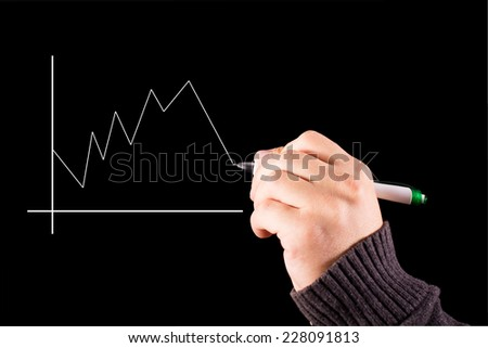 Male hand drawing a graph. - stock photo