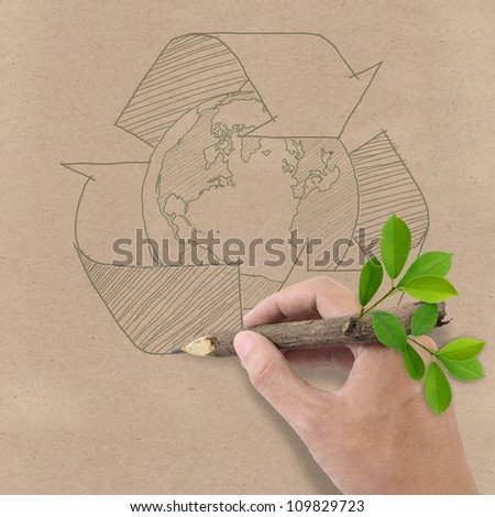 Male hand drawing recycle and earth symbol on Brown Recycled Paper. - stock photo