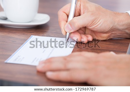 Male Hand Filling Out The Amount On A Cheque - stock photo