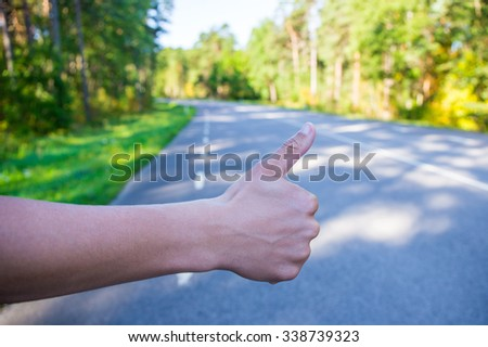 male hand hitching car on forest road - stock photo