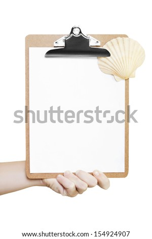 Male hand holding a clipboard with a single sheet of blank white paper and a fan-shaped seashell, conceptual of a summer vacation travel checklist - stock photo