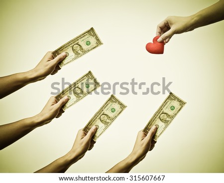 Male hand holding a dollar banknote trying to buy a red hearts from female hand - Buying love concept - stock photo