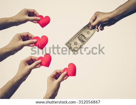Male hand holding a dollar banknote trying to buy red hearts from female hands - Buying love concept - stock photo