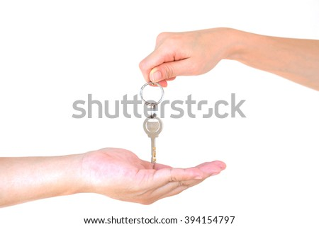 Male hand holding a key and handing it over to another person isolated - stock photo