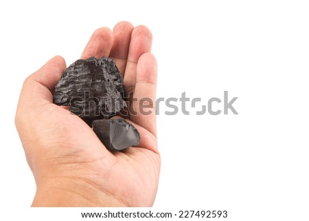 Male hand holding a lump of charcoal over white background - stock photo