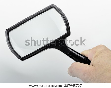 Male hand holding a old and vintage Magnifying Glass - stock photo