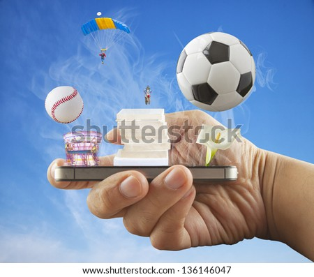 Male hand holding a smartphone, with sports and entertainment objects coming out - stock photo
