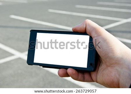 Male hand holding a smartphone with white screen at the parking lot or car park, close up. - stock photo