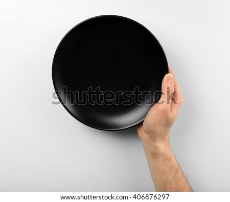 Male hand holding black plate, isolated on white - stock photo