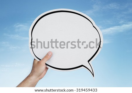 Male hand holding blank speech bubble over blue sky with copy space - stock photo