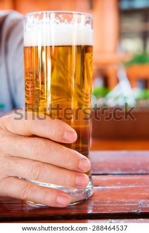 Male hand holding glass of freshly tapped beer - stock photo