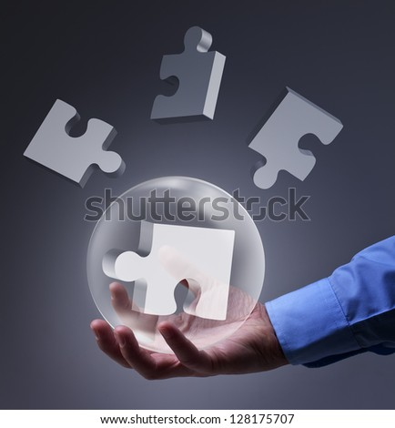 Male hand holding glass sphere with puzzle pieces - solution concept - stock photo
