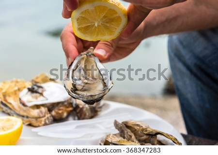 Male hand holding oysters on a plastic plate near the sea - stock photo