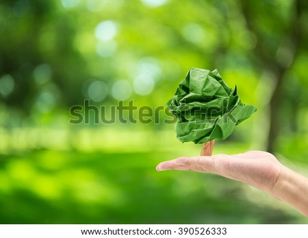 male hand holding paper shape tree on blurred green bokeh background of tree nature : world environment day - stock photo