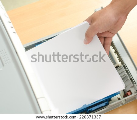 Male hand holding paper sheets into printer tray in office. - stock photo