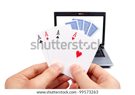 Male hand holding poker of aces and laptop with cards on the screen in the background, isolated on white - stock photo