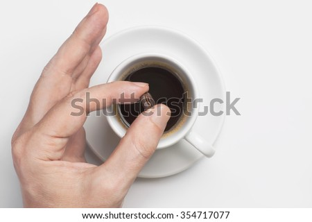 Male hand holding roasted coffee bean over cup of black coffee against white background with space for text. Top view, focus on coffee bean. Concept is best quality of natural strong coffee. - stock photo