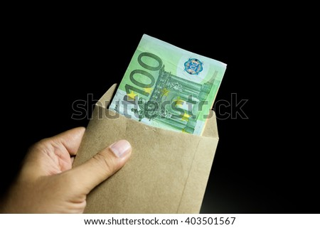 Male hand holding salary envelope euro money banknotes. - stock photo