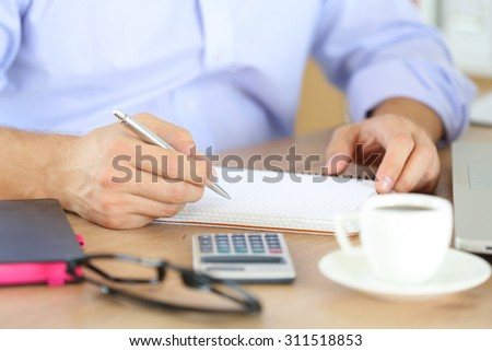 Male hand holding silver pen ready to make note in opened notebook. Businessman or employee at workplace writing business ideas, plans or tasks at personal organizer. Office life or education concept - stock photo