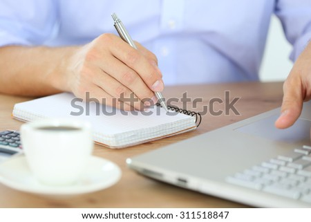 Male hand holding silver pen ready to make note in opened notebook while working at laptop computer. Businessman or employee at workplace writing business ideas, plans or tasks at personal organizer - stock photo