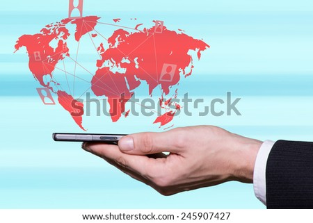 Male hand holding smartphone and world map in background - stock photo