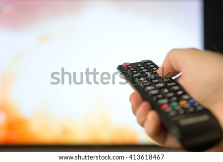 Male hand holding TV remote control. - stock photo