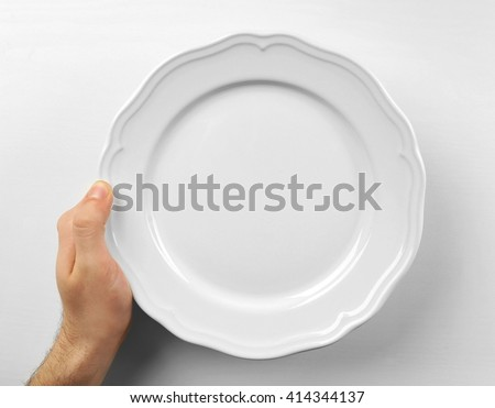 Male hand holding white plate, isolated on white - stock photo