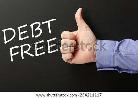 Male hand in a business shirt giving the thumbs up gesture to the phrase Debt Free written on a blackboard - stock photo