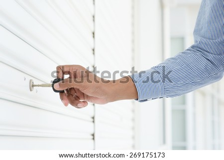 Male hand inserting key in keyhole to opening locked metal door. - stock photo