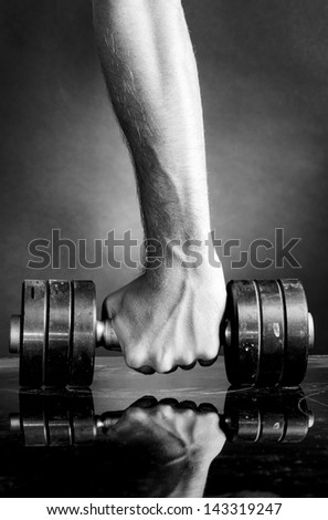 male hand is holding metal barbell on dark gray background - stock photo