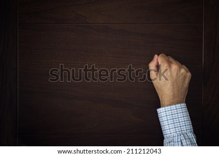 Male hand is knocking on wooden door, conceptual image. Visitor or guest is at the door. - stock photo