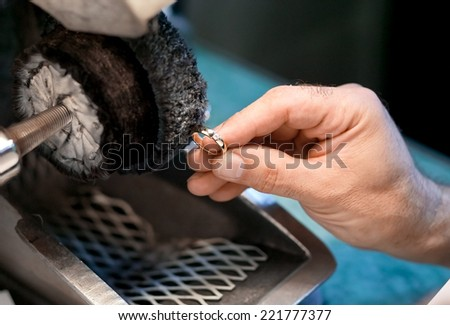 Male hand is polishing a wedding ring - stock photo