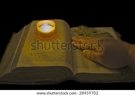 Male hand lies on ancient bible with a big christian cross in the light of a candle over black background - stock photo