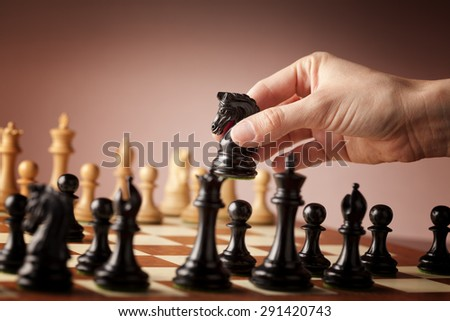 Male hand moving the black chess knight during the game of chess - stock photo